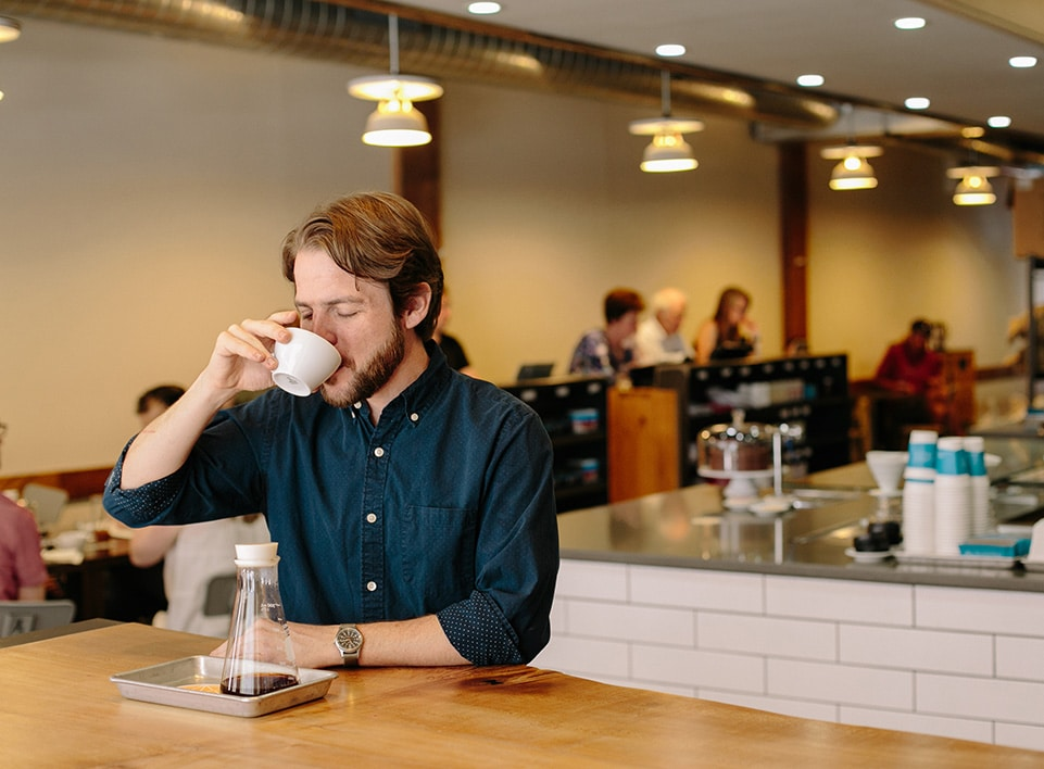 Kevin Reddy takes a moment to enjoy a cup of specialty coffee at Blueprint.