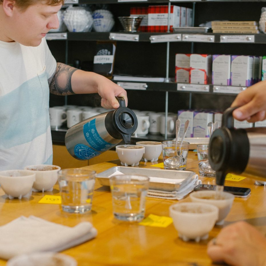 Blueprint staff pours water onto freshly ground coffee during a cupping.